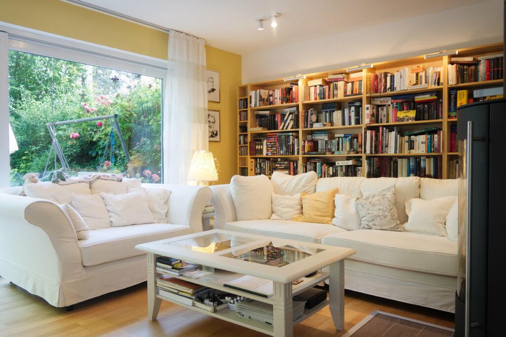 Fotografie eines gut beleuchteten, gemütlichen Wohnzimmers mit großem Fenster